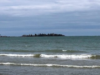 "From the opposite shoreline the now darkened ""bird cage"" lighthouse in Baileys Harbor remains part of the tree line."